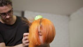 使用一hairdryer的专业头发梳妆台在理发以后 美容院的年轻红头发人妇女 慢动作射击 股票视频