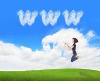 使用万维网,云彩女孩跳个人计算机片剂 库存照片