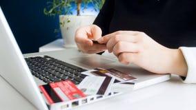 使用不同的信用卡的女实业家的特写镜头图象在网上支付 免版税图库摄影