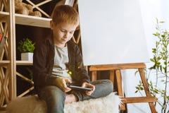 使用不同的小配件的小男孩在家 免版税库存图片