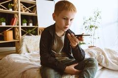 使用不同的小配件的小男孩在家 库存照片