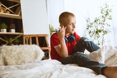 使用不同的小配件的小男孩在家 免版税库存照片