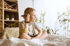 使用不同的小配件的小男孩在家 免版税图库摄影