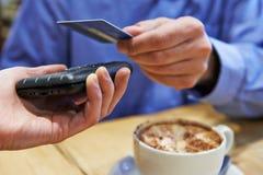 使用不接触的付款的顾客在咖啡店 库存照片