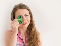 使用与一个五颜六色的手坐立不安锭床工人玩具的女孩 图库摄影