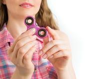 使用与一个五颜六色的手坐立不安锭床工人玩具的女孩 库存图片