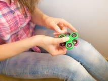 使用与一个五颜六色的手坐立不安锭床工人玩具的女孩 库存照片