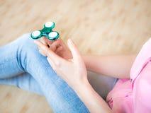 使用与一个光滑的轻的五颜六色的手坐立不安锭床工人玩具的女孩 库存图片