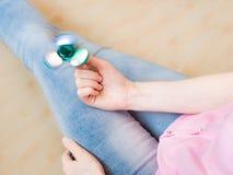 使用与一个光滑的轻的五颜六色的手坐立不安锭床工人玩具的女孩 免版税库存图片