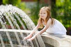 使用与一个城市喷泉的逗人喜爱的小女孩在热的夏日 库存图片