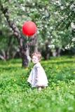 使用与一个大红色气球的滑稽的女婴 免版税图库摄影