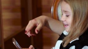 使用与一个手机的母亲和女儿,女孩打开在小配件的应用,打流动比赛 股票录像