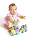 使用与一个木火车玩具的女婴 库存图片