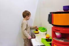 使用与一个玩具厨房的男孩在儿童居室或幼儿园 免版税图库摄影