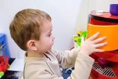 使用与一个玩具厨房的男孩在儿童居室或幼儿园 免版税库存图片