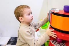 使用与一个玩具厨房的男孩在儿童居室或幼儿园 库存照片