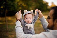 使用与一个逗人喜爱的矮小的儿子的微笑的父亲在公园 免版税库存照片