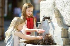 使用与一个饮用水喷泉的两个逗人喜爱的小女孩在温暖和晴朗的夏日在Desenzano del加尔达镇 库存照片