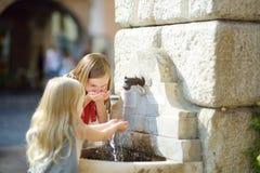 使用与一个饮用水喷泉的两个逗人喜爱的小女孩在温暖和晴朗的夏日在Desenzano del加尔达镇 图库摄影