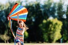 使用与一只五颜六色的风筝的微笑的小女孩在公园 免版税图库摄影