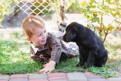 使用与一只小狗拉布拉多的小男孩在公园 免版税库存照片