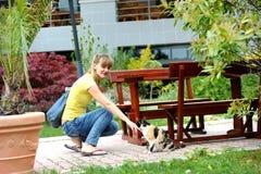 使用与一只猫的范妮女孩在公园 免版税库存照片