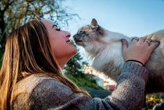 使用与一只被抢救的离群猫的美丽的女孩 图库摄影