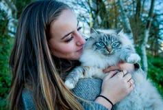 使用与一只被抢救的离群猫的美丽的女孩 免版税库存照片