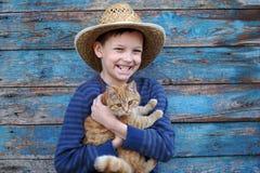 使用与一只赤褐色猫的男孩 免版税图库摄影