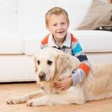使用与一只金毛猎犬的微笑的小男孩 库存照片