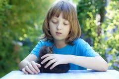 使用与一只黑小猫的男孩 免版税库存照片
