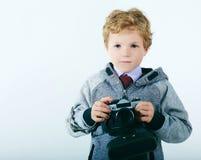 使用与一台老照相机的年轻男孩 是摄影师 免版税库存照片