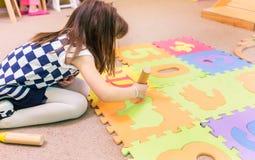 使用与一张五颜六色的难题戏剧席子的逗人喜爱的幼儿园女孩 库存照片