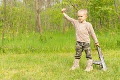 使用与一杆自动步枪的强壮男子的小男孩 免版税图库摄影