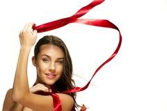 使用与一条红色丝带的愉快的美丽的妇女 免版税库存图片