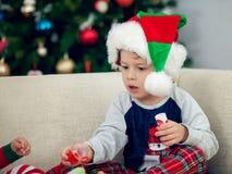 使用与一棵圣诞树的愉快的男孩在背景中 免版税图库摄影