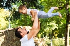 使用与一点儿子,举和保留他的父亲在野餐的头上在公园 爸爸和孩子笑 愉快 免版税库存照片