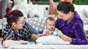 使用与一点可爱宝贝的愉快的同性父母在家说谎在地板中景 股票视频