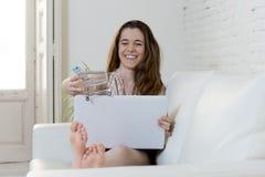 使用与一点玩具购物台车的少妇跑它在便携式计算机微笑愉快 库存照片