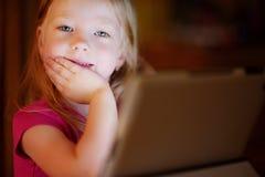 使用与一种数字式片剂的可爱的女孩在一个暗室 免版税图库摄影