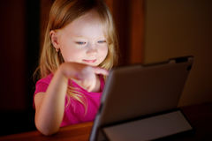 使用与一种数字式片剂的可爱的女孩在一个暗室 免版税库存照片