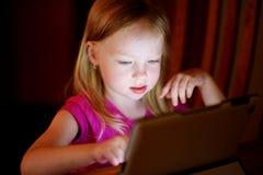 使用与一种数字式片剂的可爱的女孩在一个暗室 库存照片
