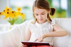 使用与一种数字式片剂的可爱的小女孩 库存图片