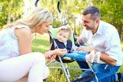 使用与一辆婴儿推车的一个婴孩的愉快的家庭在公园 图库摄影