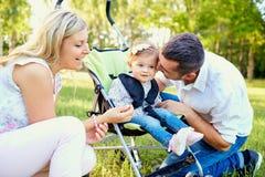 使用与一辆婴儿推车的一个婴孩的愉快的家庭在公园 库存图片
