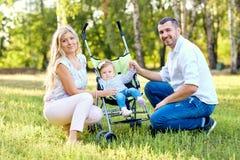 使用与一辆婴儿推车的一个婴孩的愉快的家庭在公园 免版税库存照片