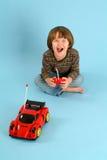 使用与一辆遥控玩具汽车的男孩 免版税库存图片