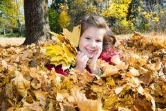 使用与下落的叶子的逗人喜爱的儿童女孩在秋天 库存图片