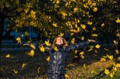 使用与下落的秋天黄色的年轻快乐的逗人喜爱的女孩妇女在公园离开在树附近,笑和微笑 免版税库存图片