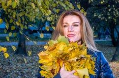 使用与下落的秋天黄色的年轻快乐的逗人喜爱的女孩妇女在公园离开在树附近,笑和微笑 图库摄影